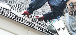 a roof repair expert working on a residential roofing