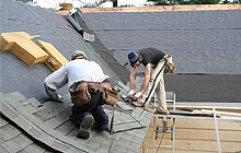 Two men working on a roof
